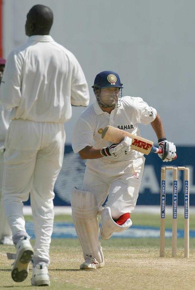 West Indies' bowler Cameron Cuffy (L) looks on India's Sachin Tendulkar scoring a run during the 2002 fifth Test Match Cricket Series 19 May 2002 at Sabina Park in Kingston, Jamaica.  AFP PHOTO/TIMOTHY A. CLARY
