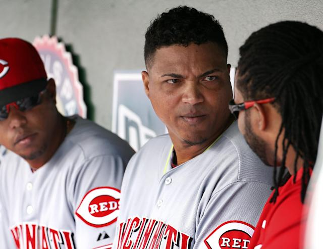 Cincinnati Reds starting pitcher Alfredo Simon, center, listens to starting pitcher Johnny Cueto, right, in the dugout during the fourth inning of a baseball game against the Washington Nationals at Nationals Park Wednesday, May 21, 2014, in Washington. (AP Photo/Alex Brandon)