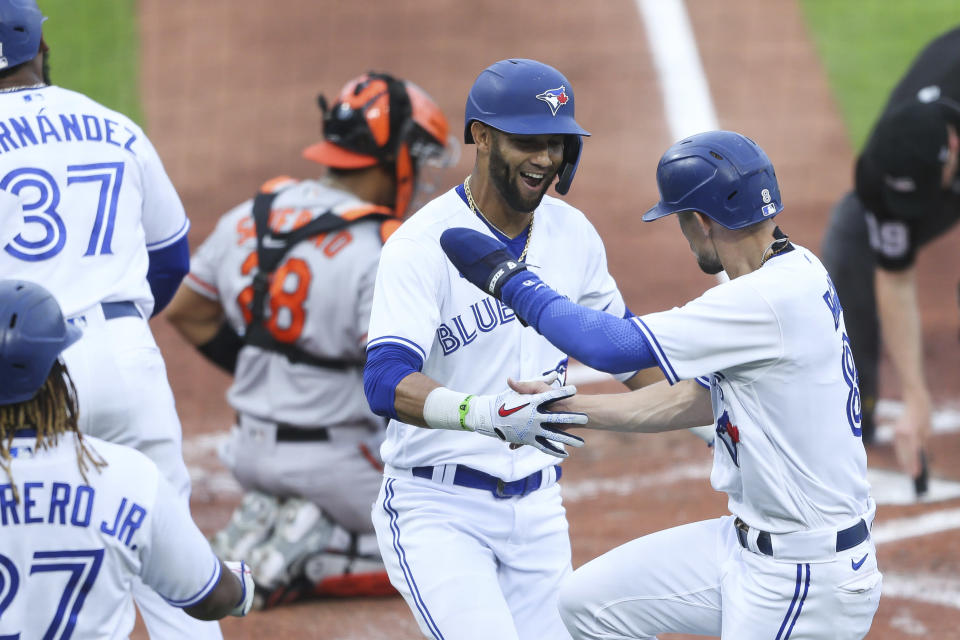 Toronto Blue Jays' Lourdes Gurriel Jr., center, celebrates with Cavan Biggio, right, after Gurriel Jr. hit a grand slam home run during the first inning of a baseball game against the Baltimore Orioles in Buffalo, N.Y., Thursday, June 24, 2021. (AP Photo/Joshua Bessex)