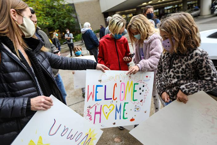 Grandchildren of Deanna Hair, Braylen, Campbell, and Landry Kaiser (left to right), grab the signs they made from their mother, Kristy Kaiser, as they wait for her to be discharged from the University of Michigan hospital in Ann Arbor, after being there for 196 days battling COVID-19 on Oct. 15, 2020.