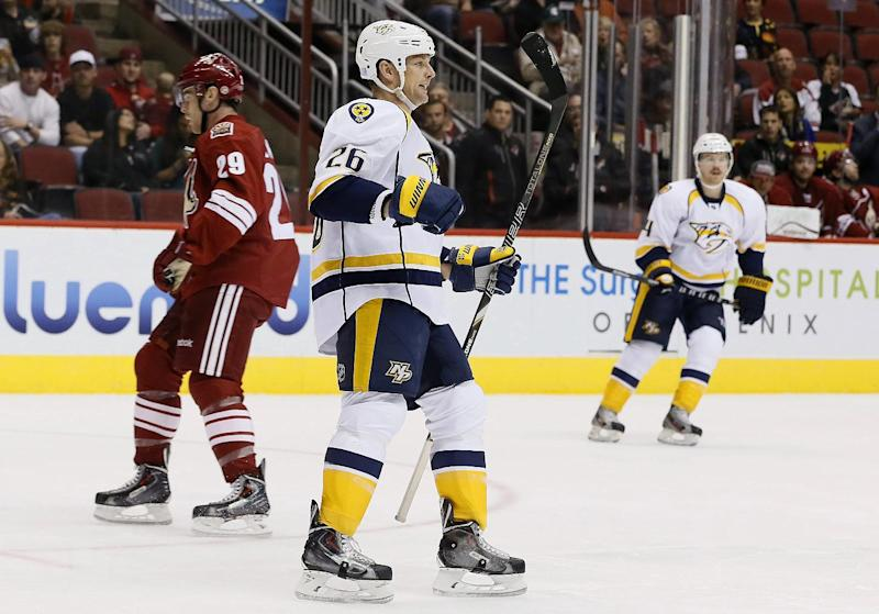 Nashville Predators' Matt Hendricks (26) skates to teammates to celebrate his goal against the Phoenix Coyotes as Coyotes' Jordan Szwarz (29) skates away and Predators' Ryan Ellis (4) skates to Hendricks during the first period of an NHL hockey game on Thursday, Oct. 31, 2013, in Glendale, Ariz. (AP Photo/Ross D. Franklin)