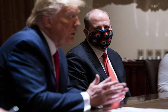 Colorado Gov. Jared Polis listens as President Donald Trump talks about reopening the country during a meeting in the Cabinet Room of the White House on Wednesday.