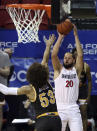 San Diego State guard Jordan Schakel (20) shoots over Wyoming guard Xavier DuSell (53) during the first half of an NCAA college basketball game in the quarterfinal round of the Mountain West Conference tournament Thursday, March 11, 2021, in Las Vegas. (AP Photo/Isaac Brekken)