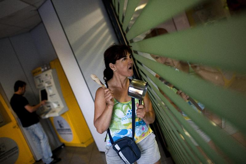 A woman hits a pot and shout slogans against bankers as a man gets money in a ATM machine, left, during a demonstration outside a Caixa bank branch in Barcelona, Spain, Friday June 8, 2012. Spain faces rising pressure to find a financial lifeline for its deeply troubled banks — likely from the eurozone's rescue fund since Madrid's borrowing costs on markets have risen sharply. (AP Photo/Emilio Morenatti)