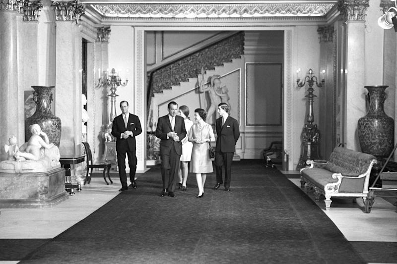 Queen Elizabeth II with American President Richard Nixon, as they walk through the corridors of Buckingham Palace on February 25, 1969. With them are the Duke of Edinburgh and Prince of Wales.
