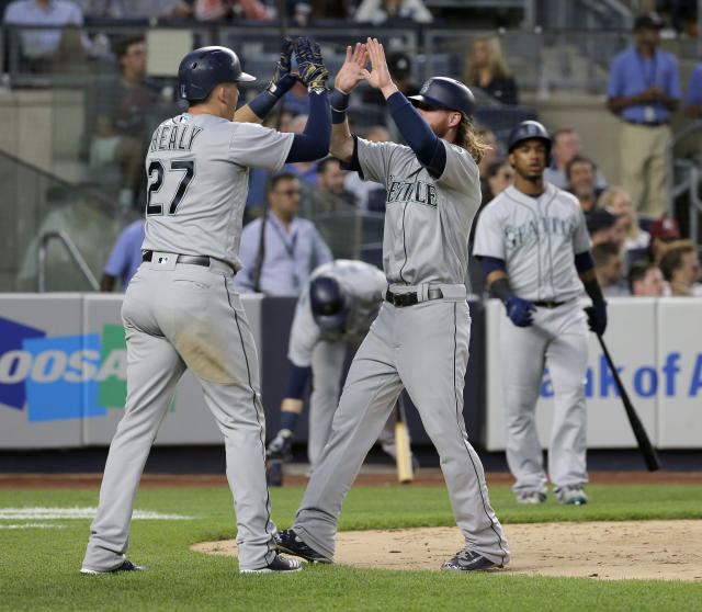 Seattle Mariners' Ryon Healy, left, and Ben Gamel celebrate after scoring on single hit by Dee Gordon during the fourth inning of a baseball game against the New York Yankees at Yankee Stadium Wednesday, June 20, 2018, in New York. (AP Photo/Seth Wenig)