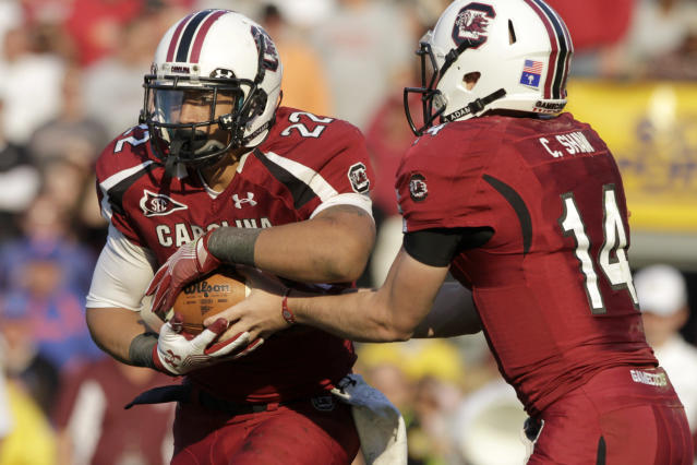 South Carolina quarterback Connor Shaw, right, hands the ball off to running back Brandon Wilds, left, during the second half of a NCAA college football game against Florida at Williams-Brice Stadium, in Columbia, S.C., Saturday, Nov. 12, 2011. (AP Photo/Brett Flashnick)