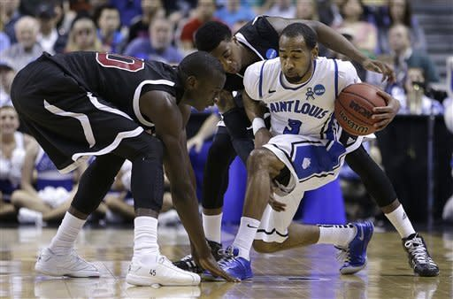 Saint Louis guard Kwamain Mitchell (3) dribbles as New Mexico State forward Bandja Sy, left, and guard Daniel Mullings defend during the first half of a second-round game in the NCAA college basketball tournament in San Jose, Calif., Thursday, March 21, 2013. (AP Photo/Ben Margot)