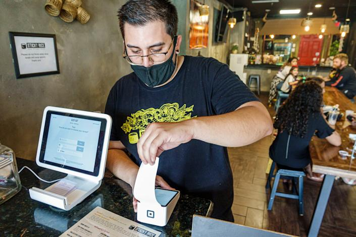 Cafe employee processes credit card payment with Square