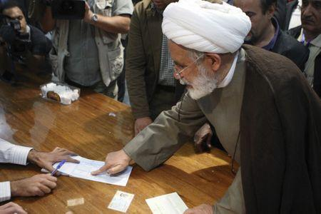 FILE PHOTO: Mehdi Karroubi places his finger print on a ballot paper during the Iranian presidential election in northern Tehran June 12, 2009. REUTERS/Chavosh Homavandi/jamejamonline