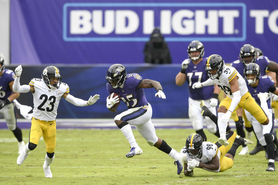 Baltimore Ravens running back Gus Edwards (35) avoids a tackle by Pittsburgh Steelers inside linebacker Vince Williams (98) while running with the ball during the first half of an NFL football game, Sunday, Nov. 1, 2020, in Baltimore. (AP Photo/Nick Wass)