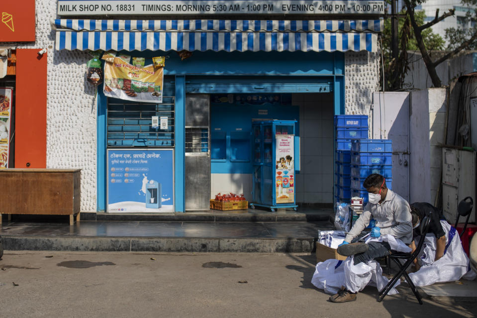An Indian health worker removes his personal protection equipment after taking nasal swab samples to test for COVID-19 during random testing of people in front of a shop at Delhi-Noida border on the outskirts of New Delhi, India, Saturday, Nov. 21, 2020. (AP Photo/Altaf Qadri)