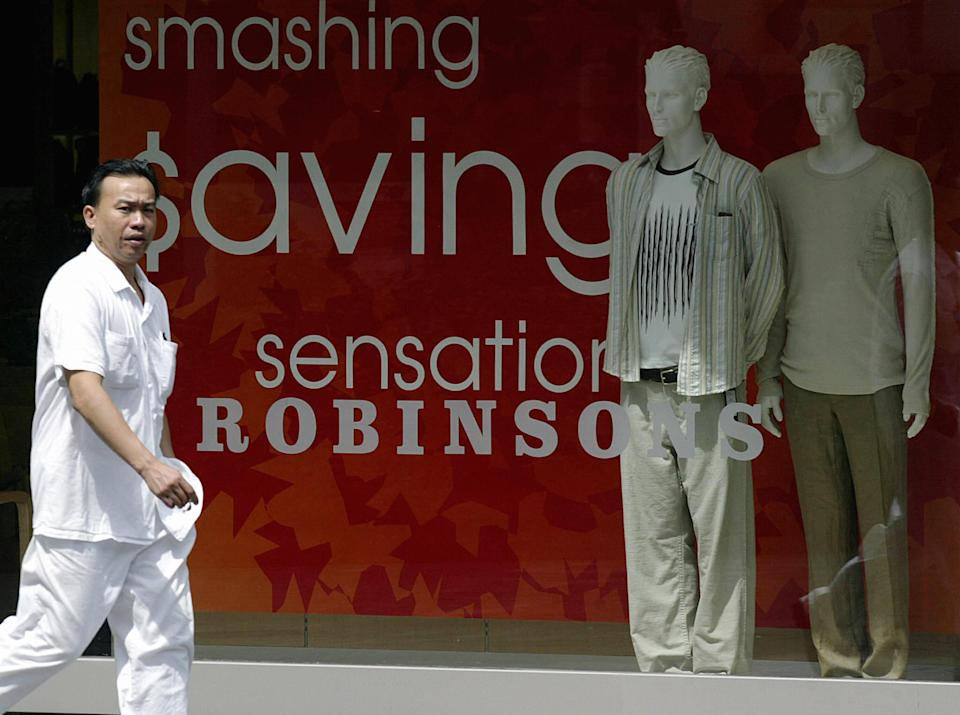 A man walks past a window display of Robinsons retail outlet in Singapore, 19 September 2003. Indonesian retailer PT Matahari Putra Prima says it is considering buying a stake in Singapore's retailer Robinson, Channel news Asia reported.  AFP PHOTO/ROSLAN RAHMAN  (Photo credit should read ROSLAN RAHMAN/AFP via Getty Images)