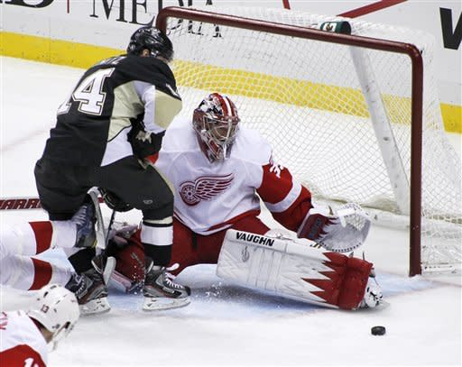 Detroit Red Wings goalie Jimmy Howard (35) stops a shot by Pittsburgh Penguins' Chris Kunitz (14) in the first period of the NHL hockey game on Tuesday, Dec. 13, 2011, in Pittsburgh. (AP Photo/Keith Srakocic)