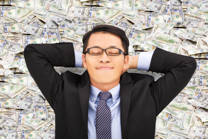 Satisfied guy in a suit resting on a pile of money.