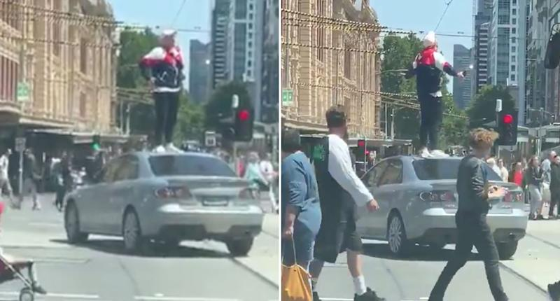 A man stands on top of a car in Melbourne's CBD.