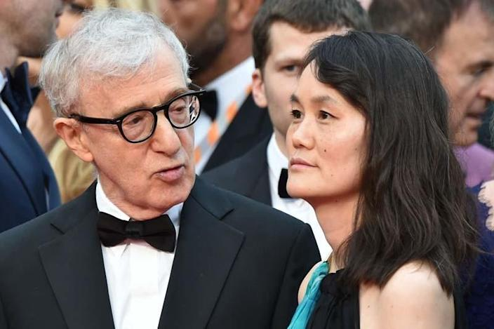 Woody Allen in a tuxedo and glasses with Soon-Yi Previn in a blue and black dress