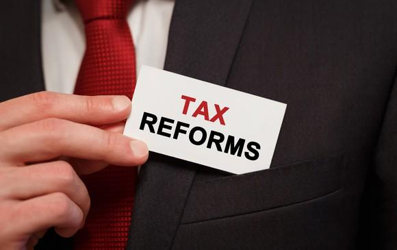 A businessman in a suit holding a business card that says tax reforms.
