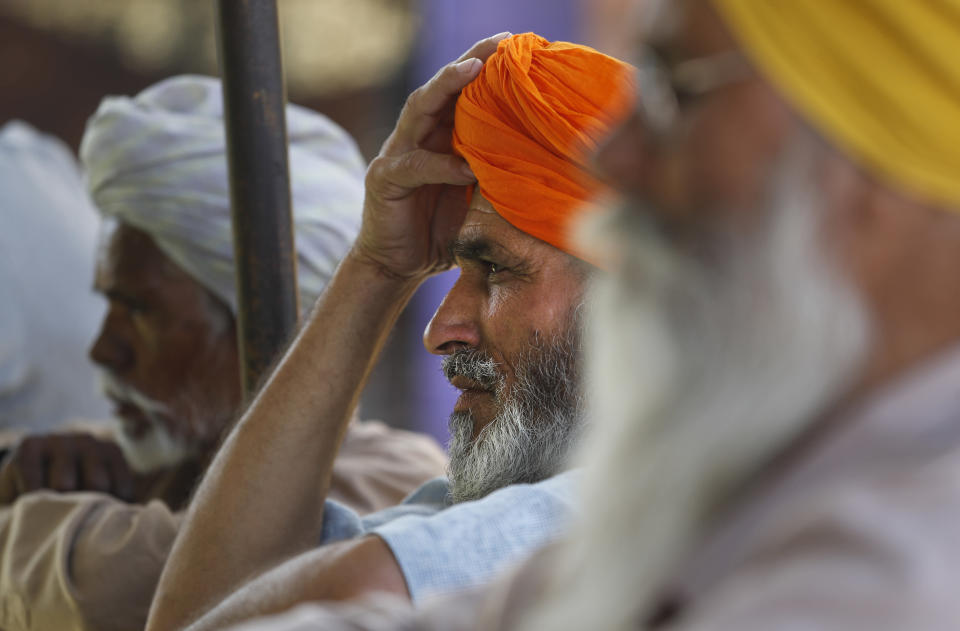 Indian farmers listen to a speaker as they camp at Singhu, along the Delhi-Haryana border, India, Friday, March 5, 2021. Saturday marks 100 days of the ongoing farmer protests against the contentious new agricultural reform laws which have led tens of thousands of farmers to blockade key highways leading to the capital. Multiple rounds of talks have failed to produce any breakthrough on the farmers' key demand to revoke the legislation. (AP Photo/Manish Swarup)