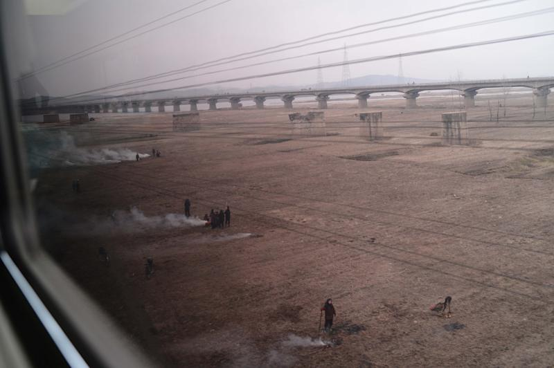 North Koreans are seen from the window of a train along the railway line between Pyongyang and the North Phyongan Province on the west coast on April 8, 2012
