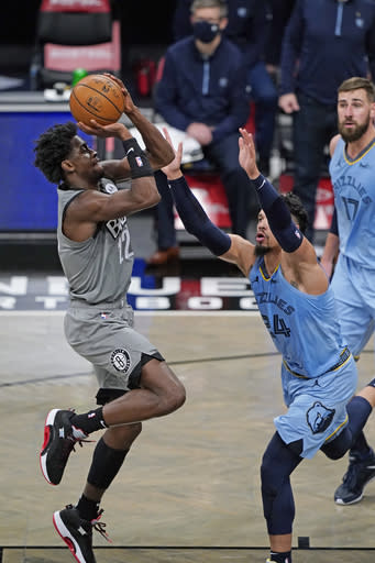 Brooklyn Nets guard Caris LeVert (22) shoots with Memphis Grizzlies guard Dillon Brooks (24) defending during the first half of an NBA basketball game Monday, Dec. 28, 2020, in New York. (AP Photo/Kathy Willens)