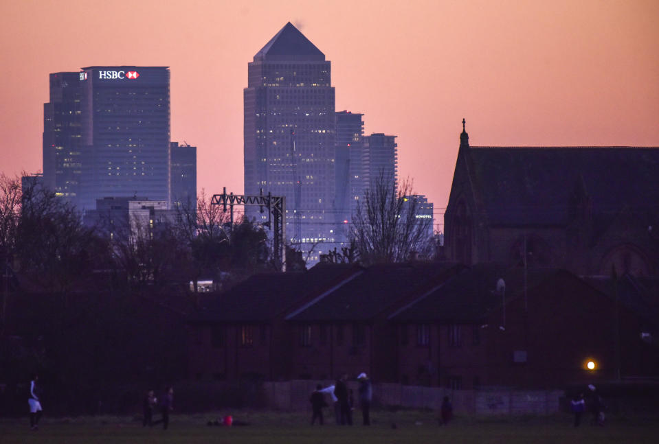 General view of the skyline of the Canary Wharf financial district as people play at Wanstead Flats at sunset, in London, Sunday, Feb. 28, 2021.(AP Photo/Alberto Pezzali)