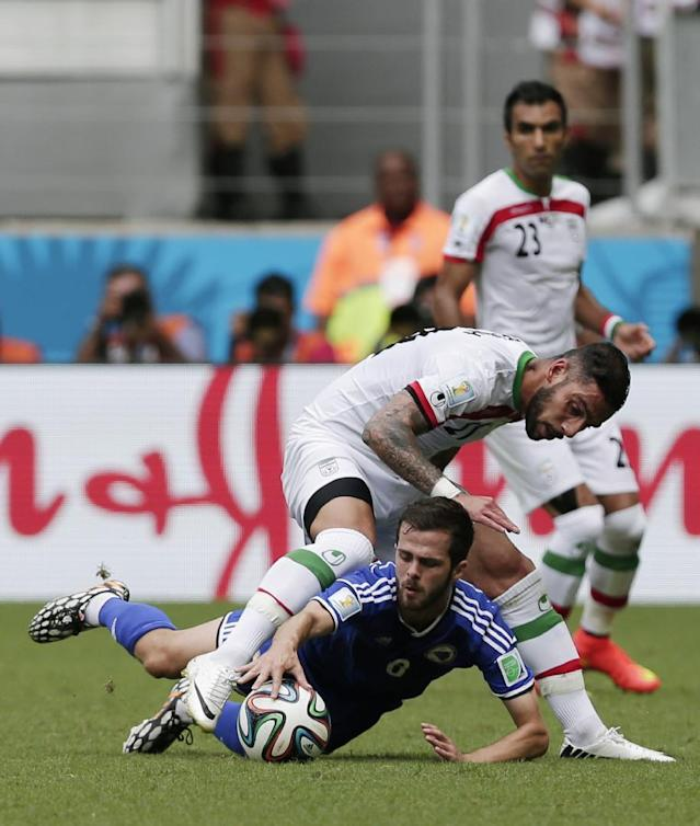 Bosnia's Miralem Pjanic grabs the ball with his hand next to Iran's Ashkan Dejagah during the group F World Cup soccer match between Bosnia and Iran at the Arena Fonte Nova in Salvador, Brazil, Wednesday, June 25, 2014. (AP Photo/Marcio Jose Sanchez)