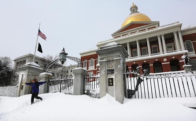 BOSTON, MA - FEBRUARY 09: A young woman jumps down from snow piled in front of the Massachusetts State House after posing for a photo following a powerful blizzard on February 9, 2013 in Boston, Massachusetts. The storm knocked out power to 650,000 and dumped more than two feet of snow in parts of New England. (Photo by Mario Tama/Getty Images)