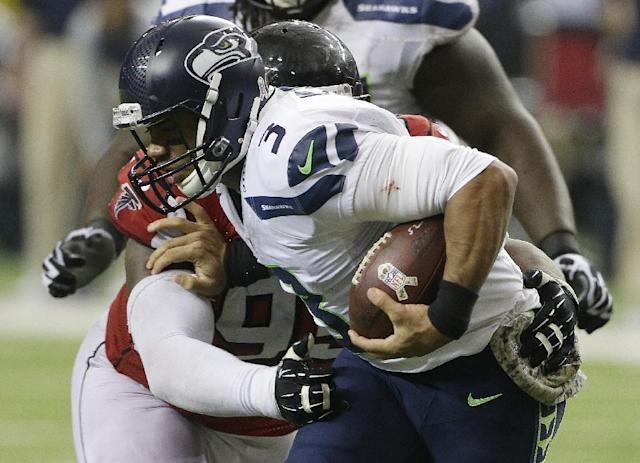 Atlanta Falcons defensive tackle Jonathan Babineaux (95) hits Seattle Seahawks quarterback Russell Wilson (3) during the second half of an NFL football game, Sunday, Nov. 10, 2013, in Atlanta. (AP Photo/John Bazemore)
