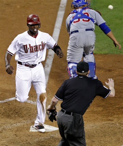 Arizona Diamondbacks' Justin Upton scores on a base hit by teammate John McDonald as Chicago Cubs catcher Wellington Castillo makes the catch during the eighth inning of a baseball game, Friday, Sept. 28, 2012, in Phoenix. (AP Photo/Matt York)