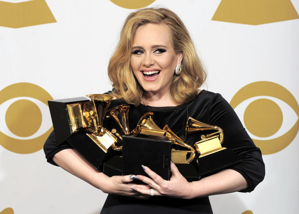 """FILE - This is a Sunday, Feb. 12, 2012  file photo of Adele  as she poses backstage with her six awards at the 54th annual Grammy Awards on Sunday, Feb. 12, 2012 in Los Angeles. Adele won awards for best pop solo performance for """"Someone Like You,"""" song of the year, record of the year, and best short form music video for """"Rolling in the Deep,"""" and album of the year and best pop vocal album for """"21."""" Adele is getting a new medal to go alongside her Grammys and Academy Award _ an honor from Queen Elizabeth II. The """"Rumor Has It"""" and """"Skyfall"""" singer was named a Member of the Order of the British Empire, or MBE on Friday June 14, 2013  in the queen's annual Birthday Honors list. (AP Photo/Mark J. Terrill, File)"""