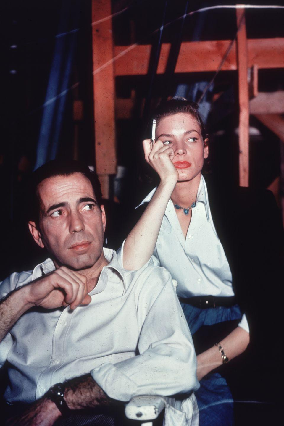 """<p>Lauren Bacall leans on the shoulder of her husband and costar, Humphrey Bogart, while waiting on the set of their film <em>Key Largo</em>. After <a href=""""https://www.harpersbazaar.com/celebrity/g31038655/lauren-bacall-life-in-photos/?slide=9"""" rel=""""nofollow noopener"""" target=""""_blank"""" data-ylk=""""slk:meeting on the set"""" class=""""link rapid-noclick-resp"""">meeting on the set</a> of <em>To Have and Have Not</em><em>, </em>this was the couple's third collaboration. </p>"""