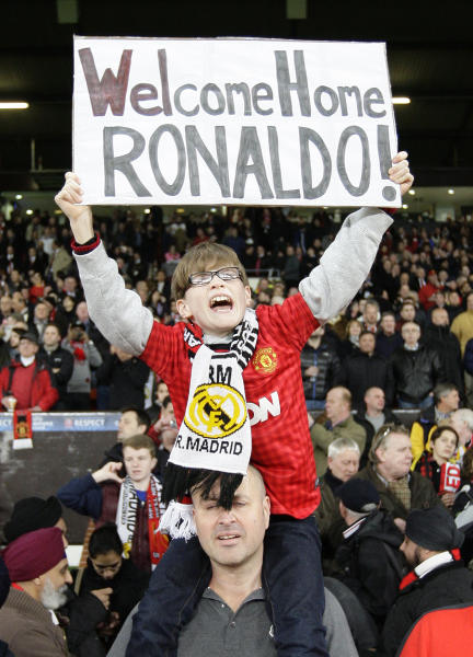 A young supporter holds a banner welcoming Real Madrid and former Manchester United player Cristiano Ronaldo ahead of the Champions League round of 16 soccer match against Manchester United at Old Trafford Stadium, Manchester, England, Tuesday, March 5, 2013. (AP Photo/Jon Super)