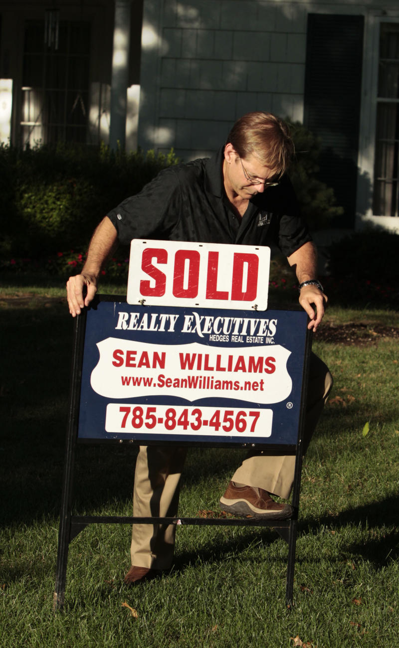 In this July 13, 2011 photo, realtor Sean Williams posts a sold sign on a home he sold in Lawrence, Kan.  Fewer people bought previously occupied homes in June, a grim sign that the worst of the housing crisis might not be over. (AP Photo/Orlin Wagner)
