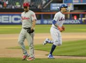 New York Mets' Wilmer Flores (4) runs the bases after hitting a walk-off home run as Philadelphia Phillies relief pitcher Victor Arano (64) leaves the field during the tenth inning in the first game of a baseball doubleheader Monday, July 9, 2018, in New York. The Mets won 4-3. (AP Photo/Frank Franklin II)
