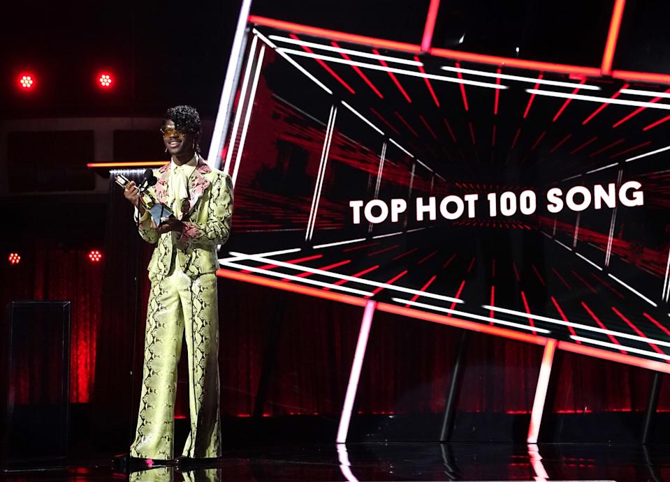 Lil Nas X, in gold patterned pants and jacket, holds his award.