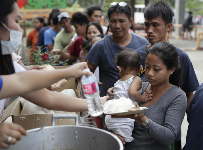 Evacuees receive a meal at an evacuation center at Santa Teresita, Batangas province, southern Philippines on Thursday Jan. 16, 2020. Taal volcano belched smaller plumes of ash Thursday but shuddered continuously with earthquakes and cracked roads in nearby towns, which were blockaded by police due to fears of a bigger eruption. (AP Photo/Aaron Favila)