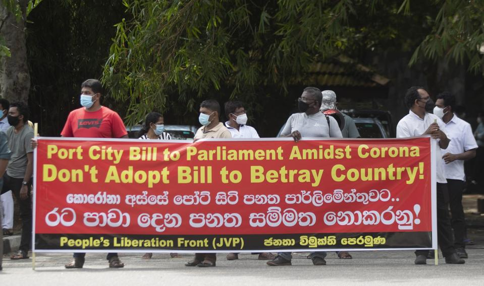 Nearly two dozen protestors belonging to the People's Liberation Front display a banner against the Chinese built port city project in Colombo, Sri Lanka, Wednesday, May 19, 2021. Sri Lanka's top court has ruled that some provisions of legislation to set up a powerful economic commission in a Chinese-built port city violate the constitution and require approval by a public referendum to become law. (AP Photo/Eranga Jayawardena)