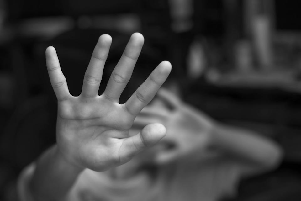 Boy showing STOP gesture with his hand. Concept of domestic violence and child abuse. Copy space