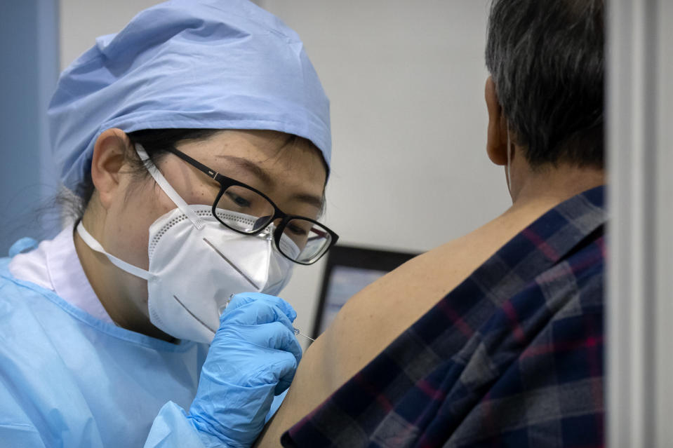 A medical worker gives a coronavirus vaccine shot to a patient at a vaccination facility in Beijing, Friday, Jan. 15, 2021. A city in northern China is building a 3,000-unit quarantine facility to deal with an anticipated overflow of patients as COVID-19 cases rise ahead of the Lunar New Year travel rush. (AP Photo/Mark Schiefelbein)