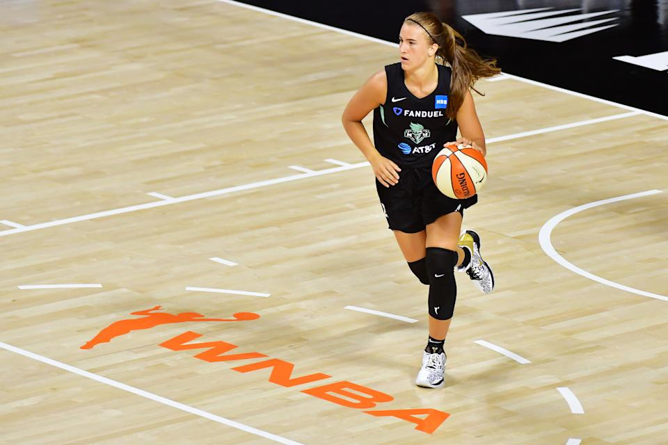 Sabrina Ionescu brings the ball up the court during a WNBA game.