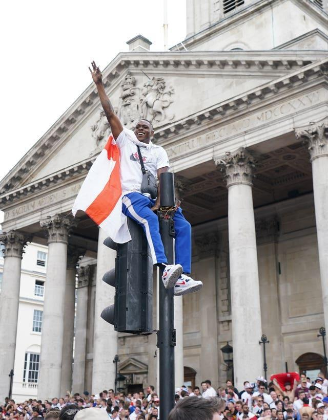 One fan climbed a traffic light in Trafalgar Square as the atmosphere ramped up (Andrew Matthews/PA)