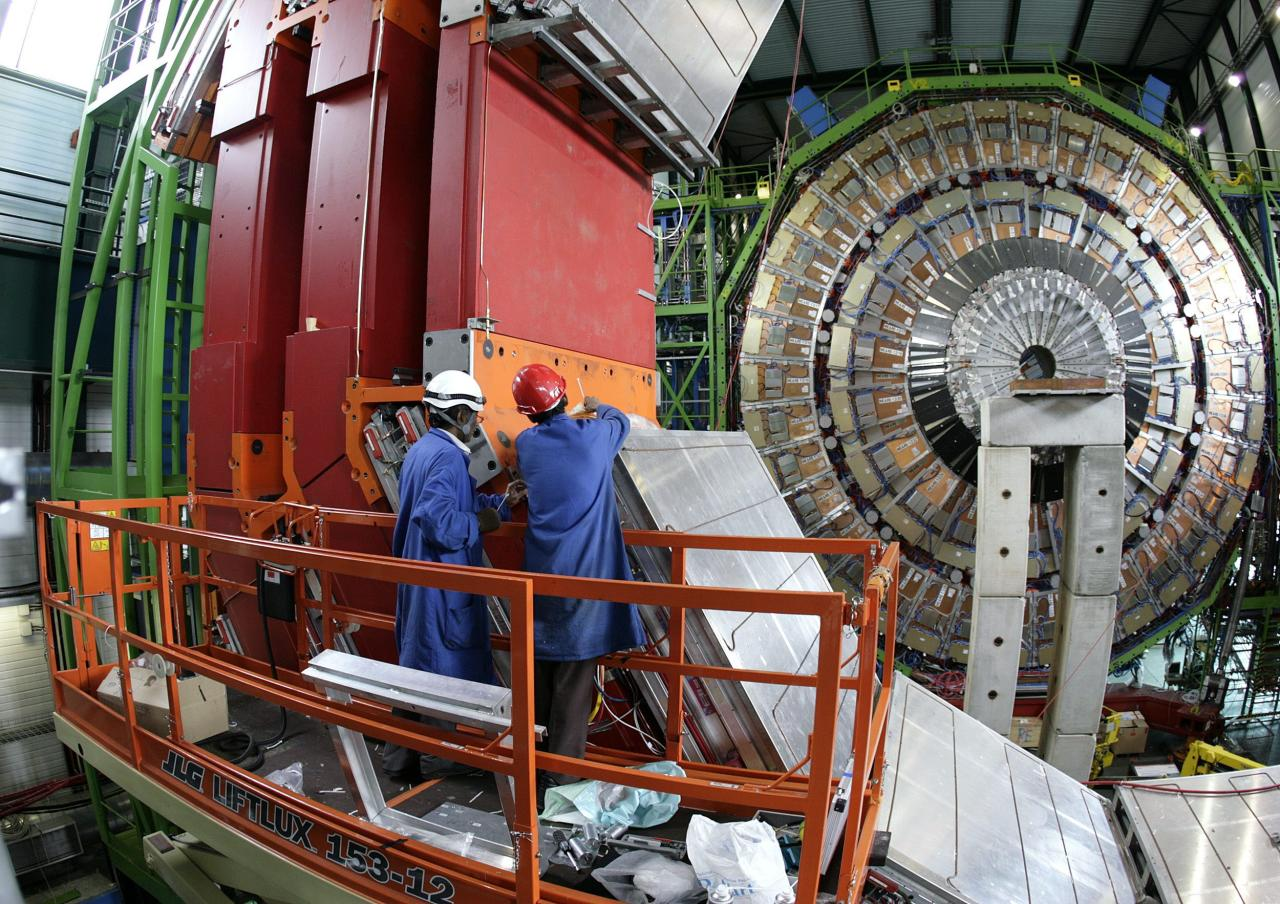 FILE - In this Thursday, March 22, 2007 file photo two engineers works to assemble one of the layers of the world's largest superconducting solenoid magnet (CMS, Compact Muon Solenoid) at the European Organization for Nuclear Research (CERN)'s Large Hadron Collider (LHC) particule accelerator, in Geneva, Switzerland. Scientists at CERN will hold a public seminar Tuesday Dec. 13, 2011 to present their latest findings from the search for an elusive sub-atomic particle known as the Higgs boson. Physicists are increasingly confident that they have narrowed down the place where it will be found and may even already have hints at its existence hidden away in reams of data. (AP Photo/KEYSTONE/Martial Trezzini, File)
