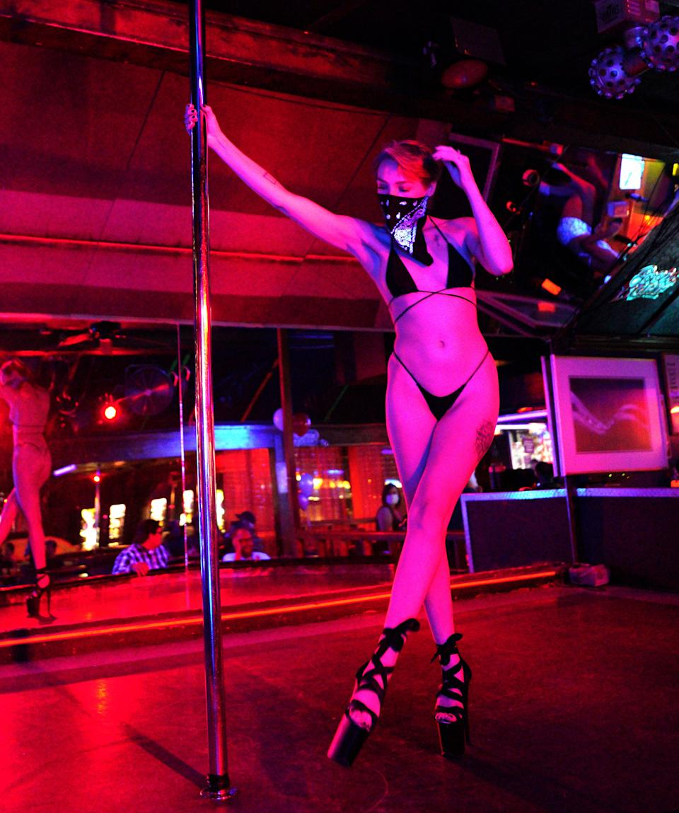 """Cleo, a dancer at The Den strip club in Cheyenne, Wyoming, works the pole while wearing a mask during the club's reopening Friday night. The club hosted a """"masks on, clothes off"""" party to celebrate."""