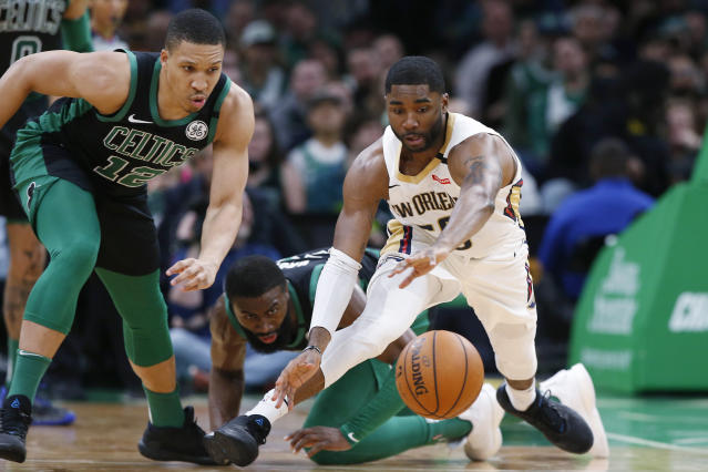 New Orleans Pelicans' E'Twaun Moore goes for a loose ball next to Boston Celtics' Grant Williams (12) and Jaylen Brown during the first quarter of an NBA basketball game Saturday, Jan. 11, 2020, in Boston. (AP Photo/Winslow Townson)
