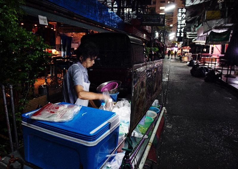 A street vendor tends to her cooking in a near deserted Soi Cowboy on October 15, 2016 (AFP Photo/Roberto Schmidt)