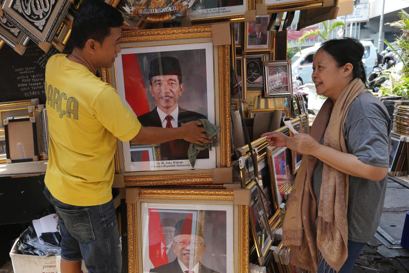 In this Wednesday. Oct. 16, 2019, photo, a vendor talks to a customer as he cleans a portrait of Indonesian President Joko Widodo and Vice President-elect Ma'ruf Amin, bottom, displayed at his stall in Jakarta, Indonesia. Known for his down-to-earth style with a reputation for clean governance, Widodo's signature policy has been improving Indonesia's inadequate infrastructure and reducing poverty, which afflicts close to a tenth of Indonesia's nearly 270 million people. But raising money would be harder at a time of global economic slowdown, major trade conflicts and falling exports. (AP Photo/Tatan Syuflana)