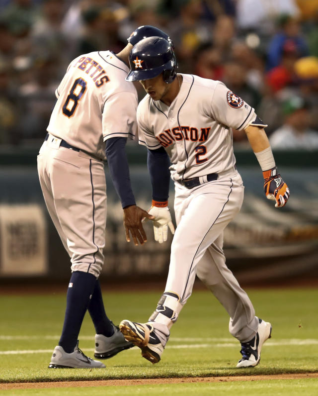 Houston Astros' Alex Bregman, right, celebrates with third base coach Gary Pettis (8) after hitting a home run off Oakland Athletics' Edwin Jackson in the fourth inning of a baseball game Friday, Aug. 17, 2018, in Oakland, Calif. (AP Photo/Ben Margot)
