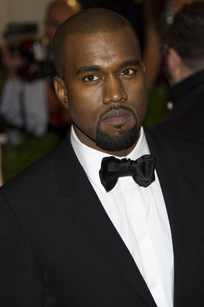 FILE - In this May 7, 2012 file photo, Kanye West arrives at the Metropolitan Museum of Art Costume Institute gala benefit, celebrating Elsa Schiaparelli and Miuccia Prada, in New York. West was sued Wednesday, Aug. 21, 2013 by Daniel Ramos, a paparazzo who claims his right hip was injured in an altercation with the rapper at Los Angeles International Airport in July. (AP Photo/Charles Sykes, File)