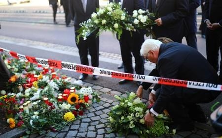 Saxony-Anhalt State Premier Reiner Haseloff, German President Frank-Walter Steinmeier and his wife Elke Budenbender lay flowers outside a kebab shop in Halle